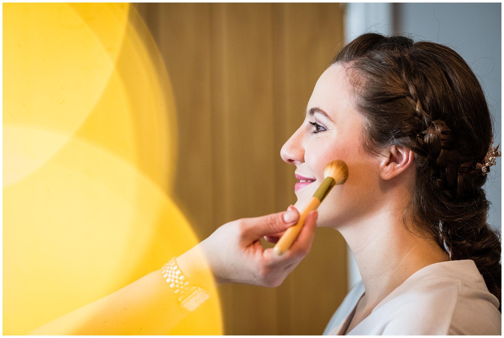 finishing touches to wedding makeup