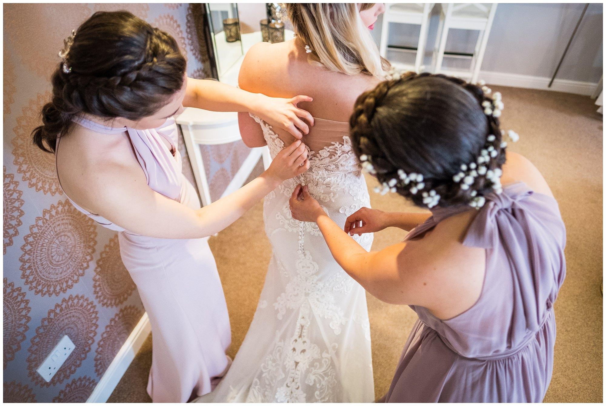 bridesmaids helping with wedding dress