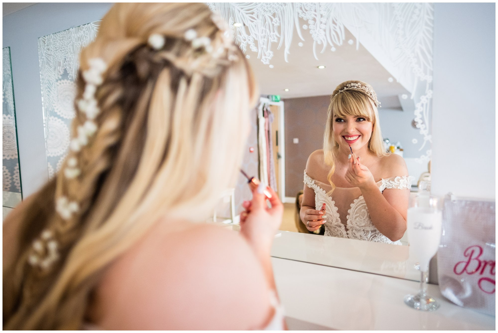 bride putting finishing touches to her lips