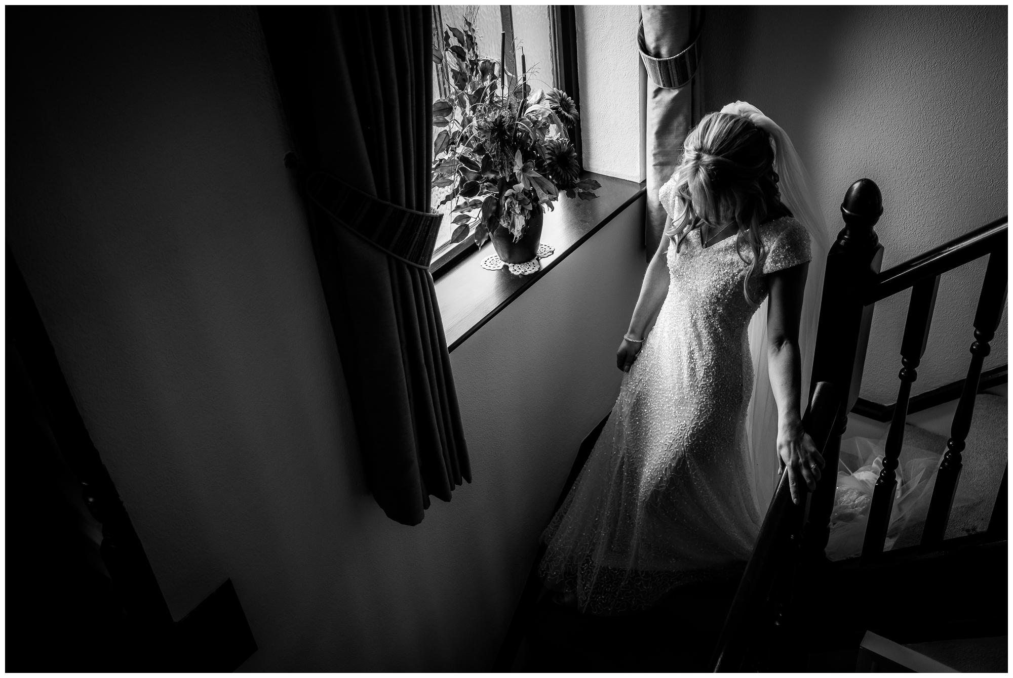 bride in dress walking down stairs