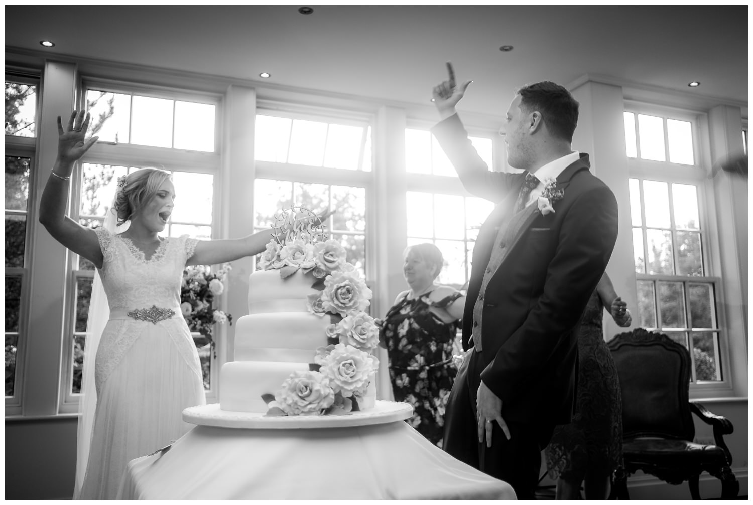 bride and groom cheering after cutting their wedding cake