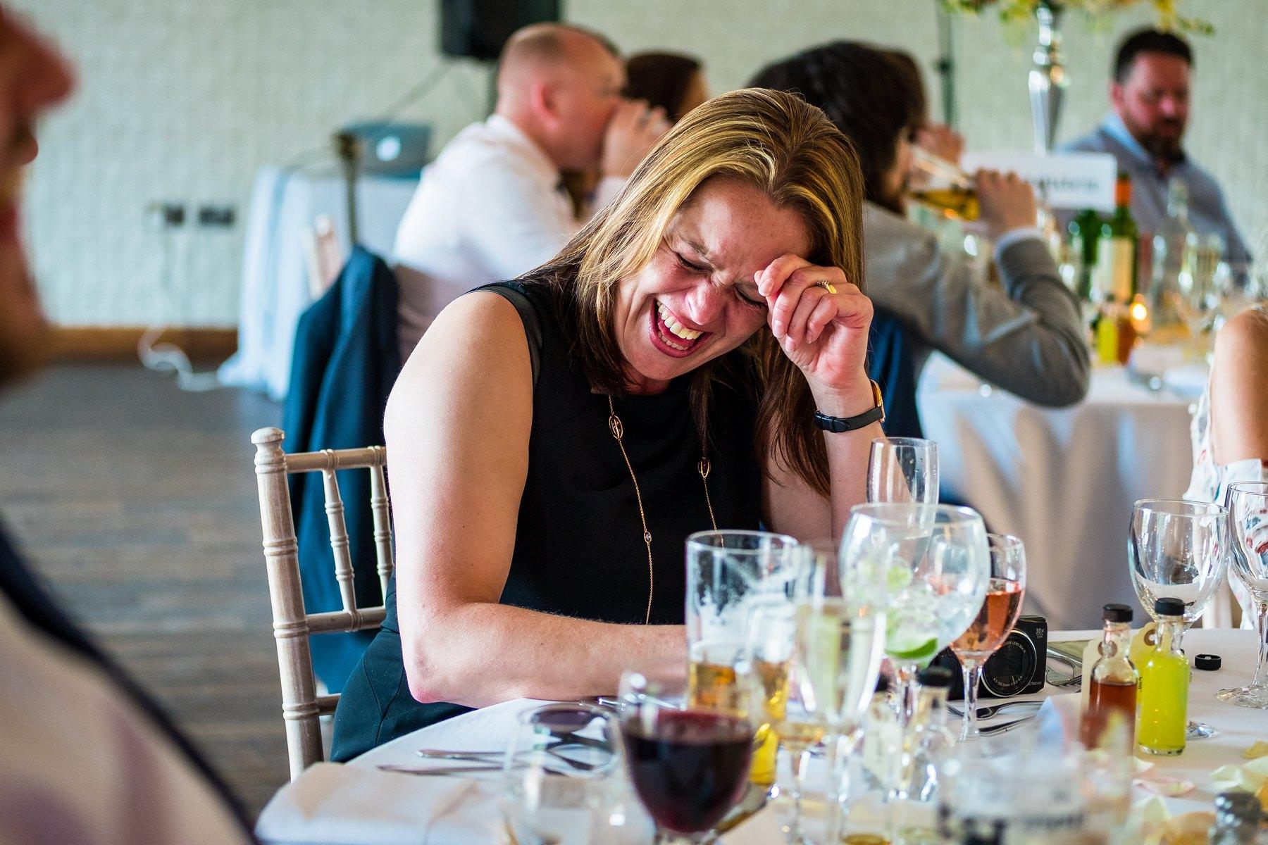 guest laughing during best man speech