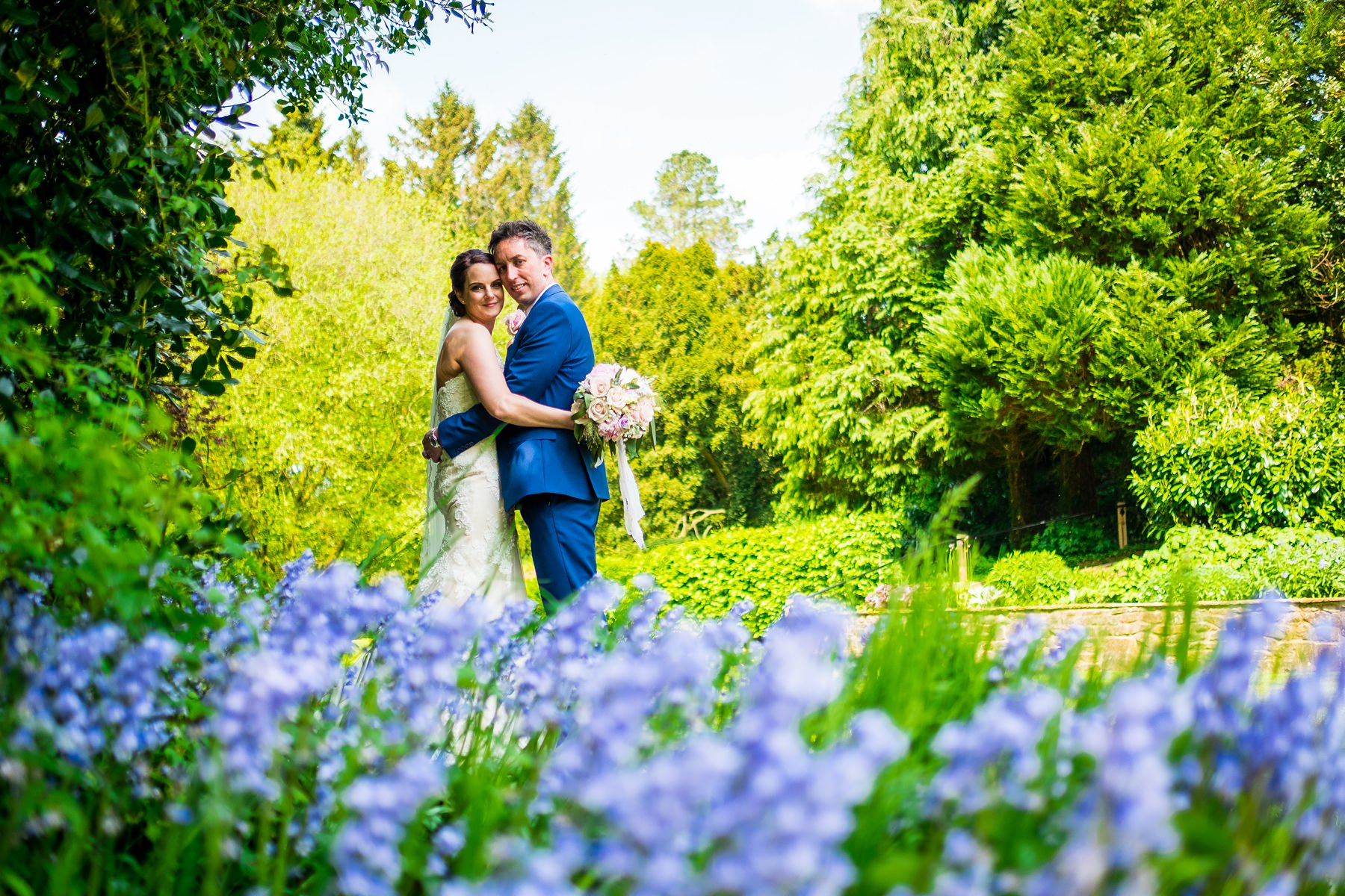 bride and groom with blue bells at mitton hall