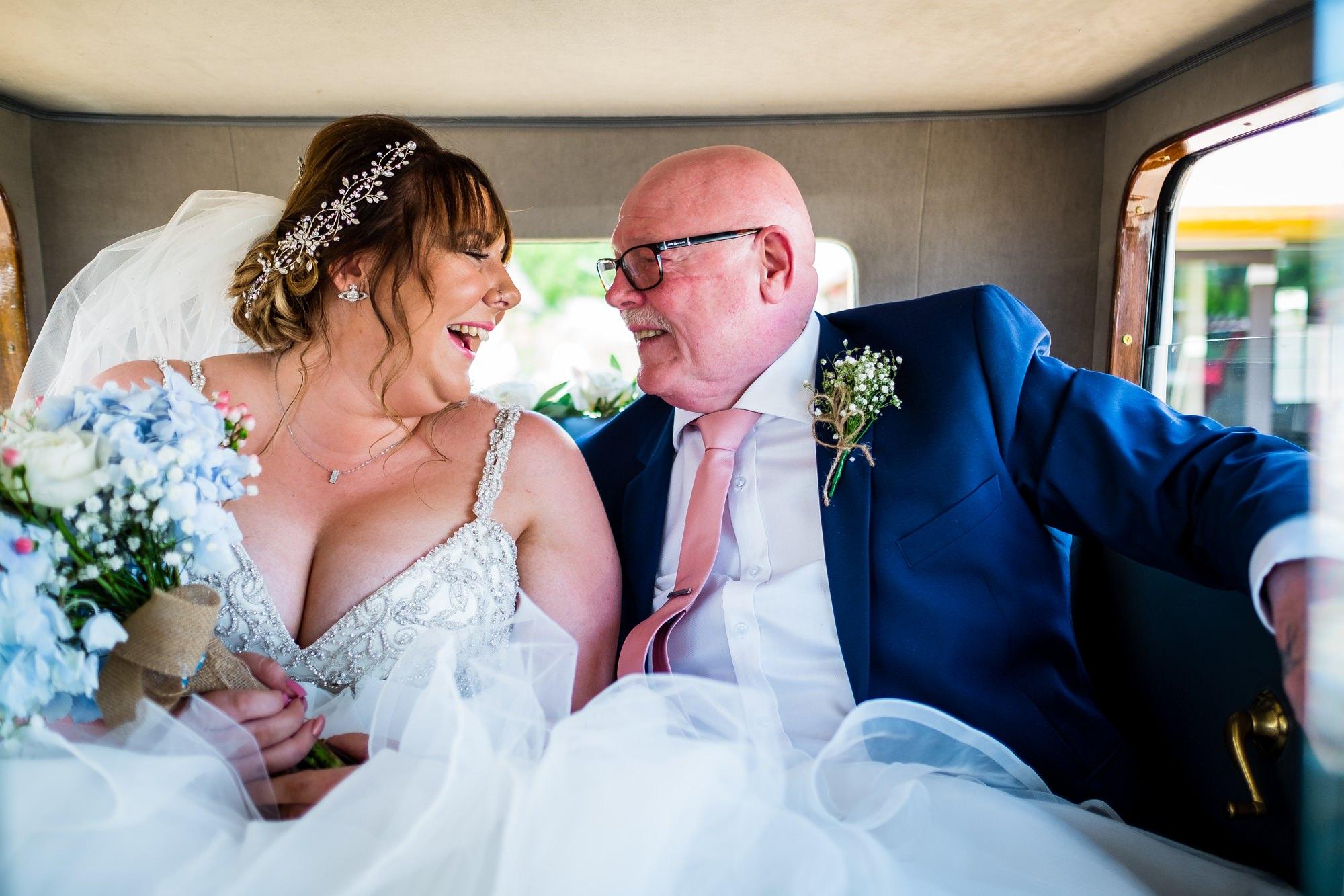bride in wedding car with dad