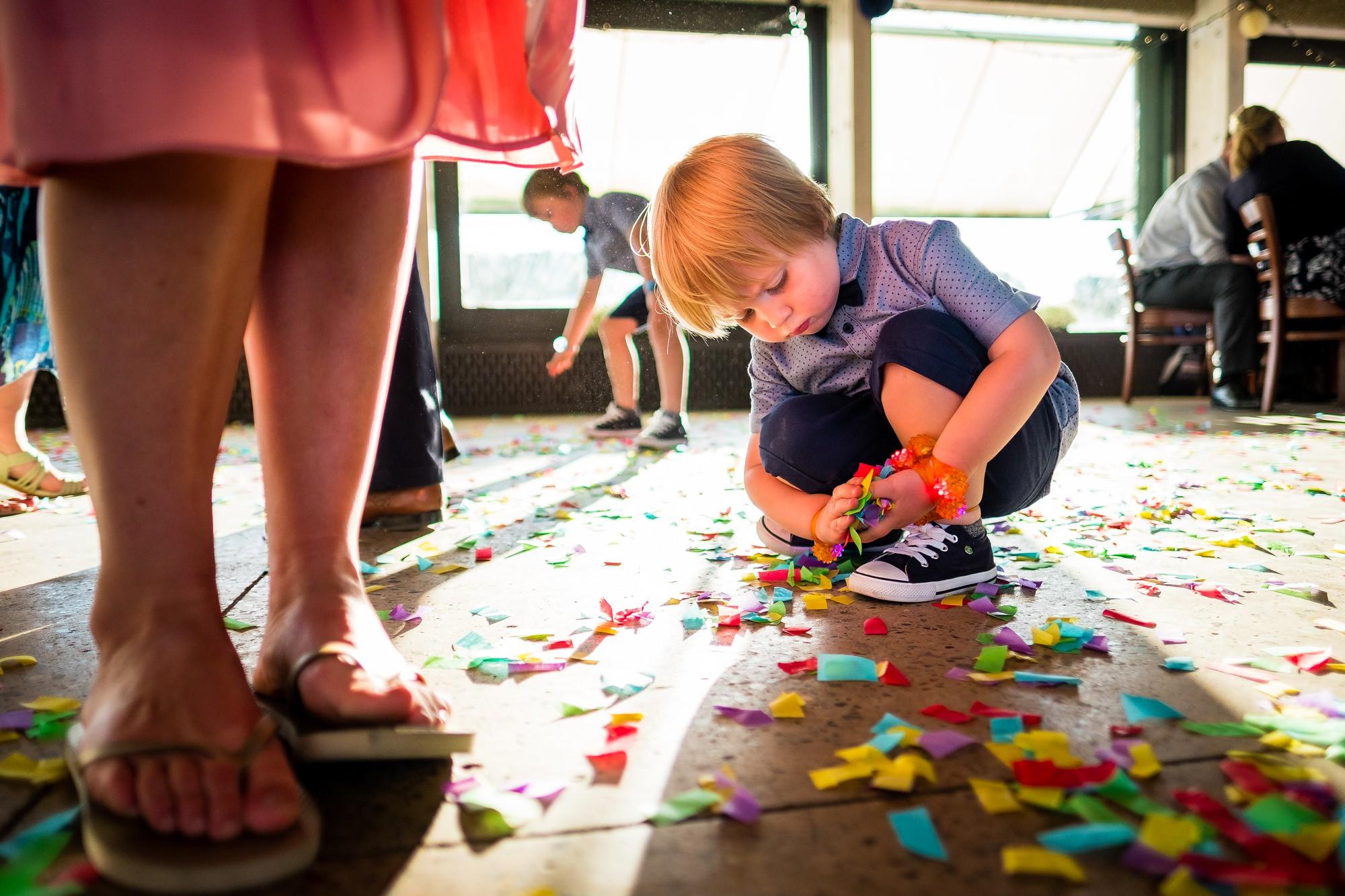 little boy picking up confetti