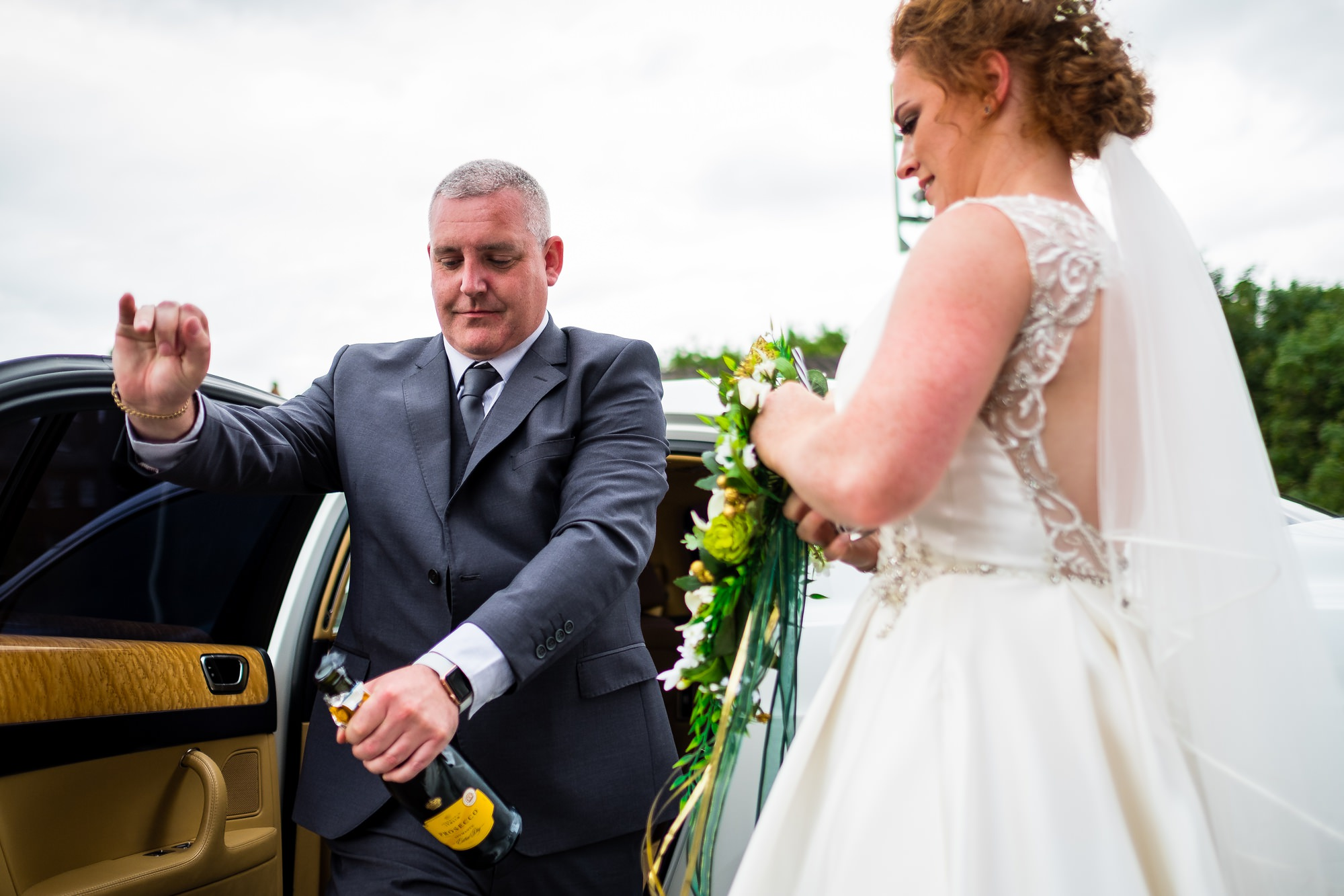 bride waiting for bottle to open before getting into wedding car