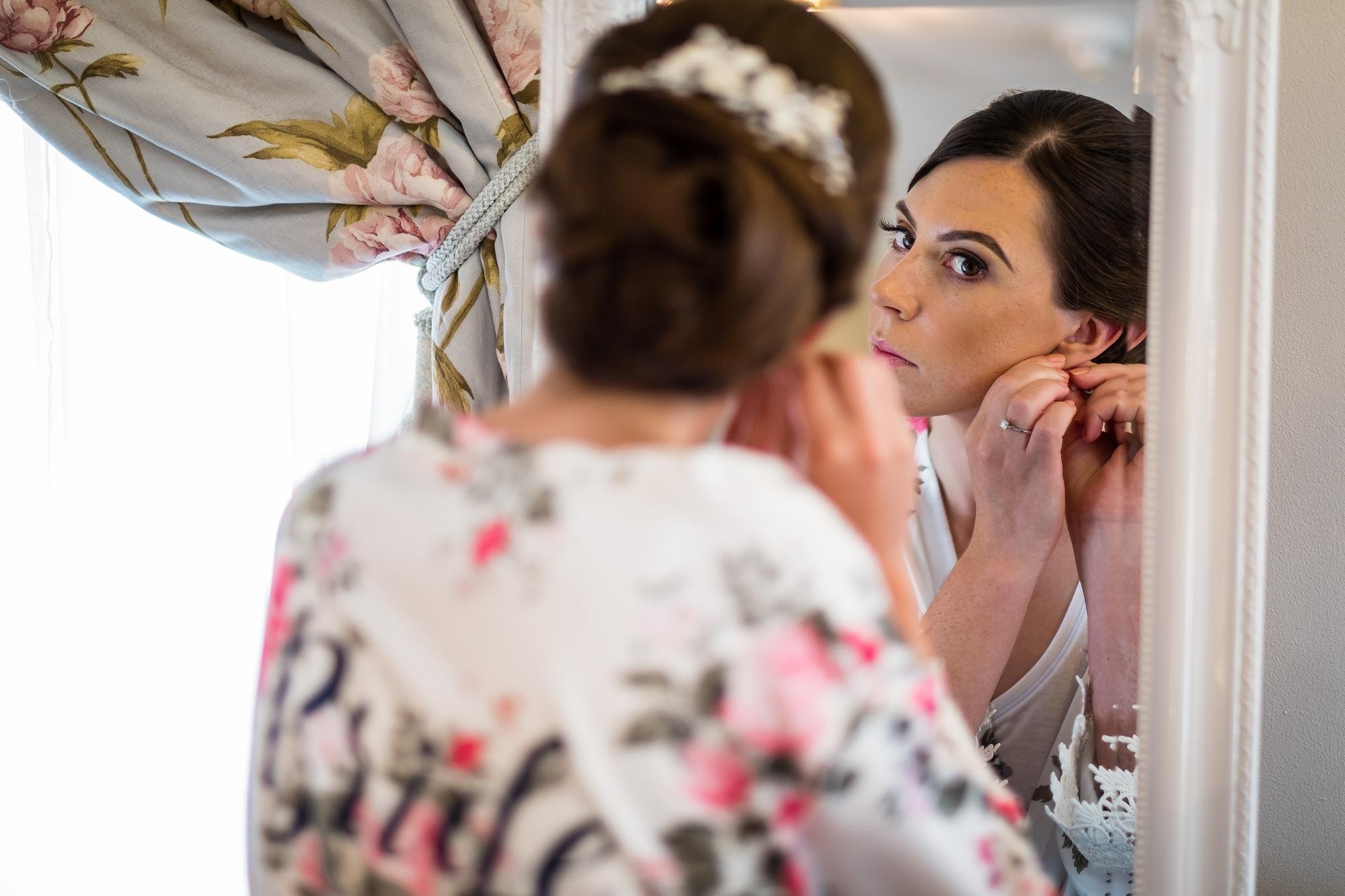 bride putting in wedding earrings
