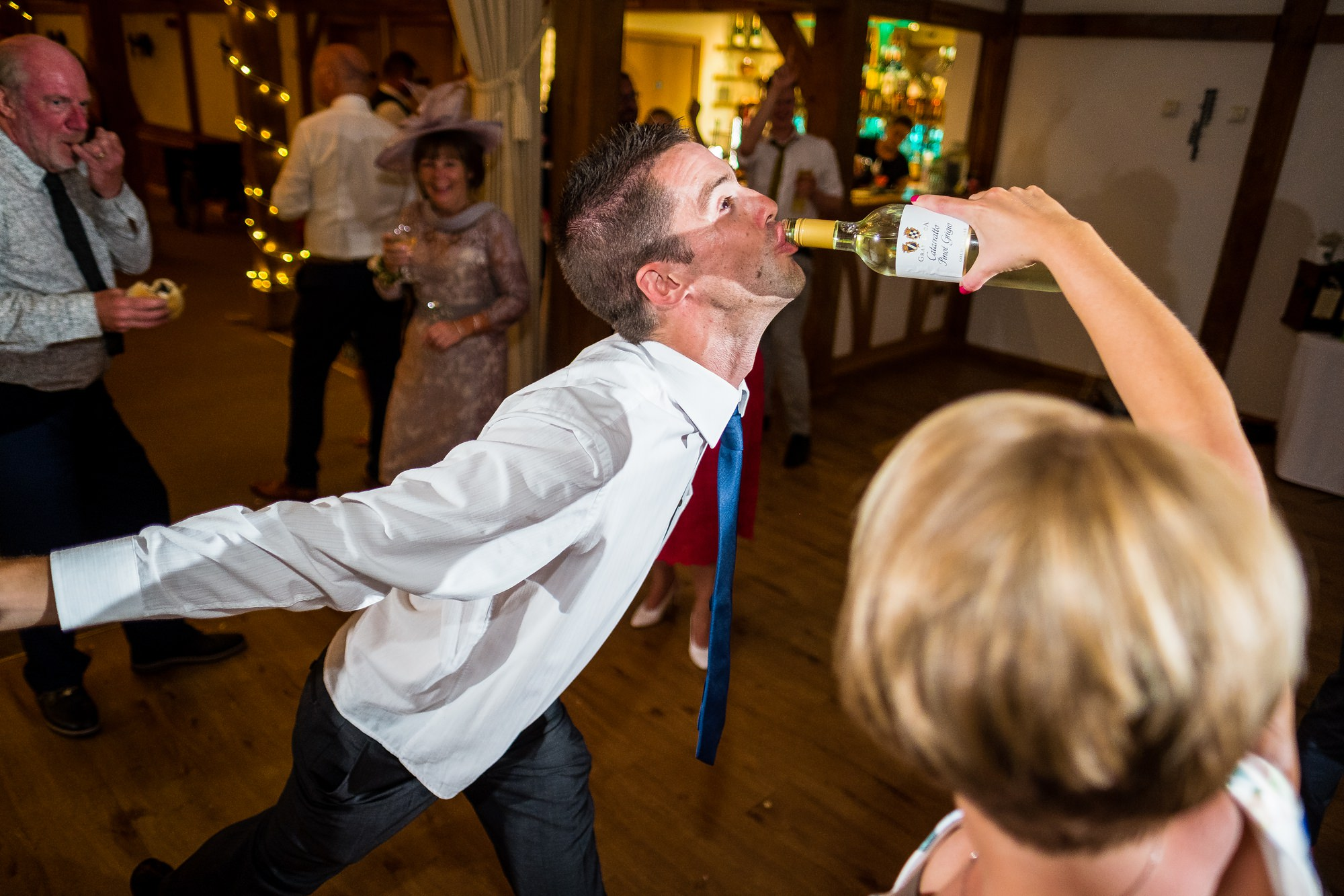 guest pouring wine in guests mouth
