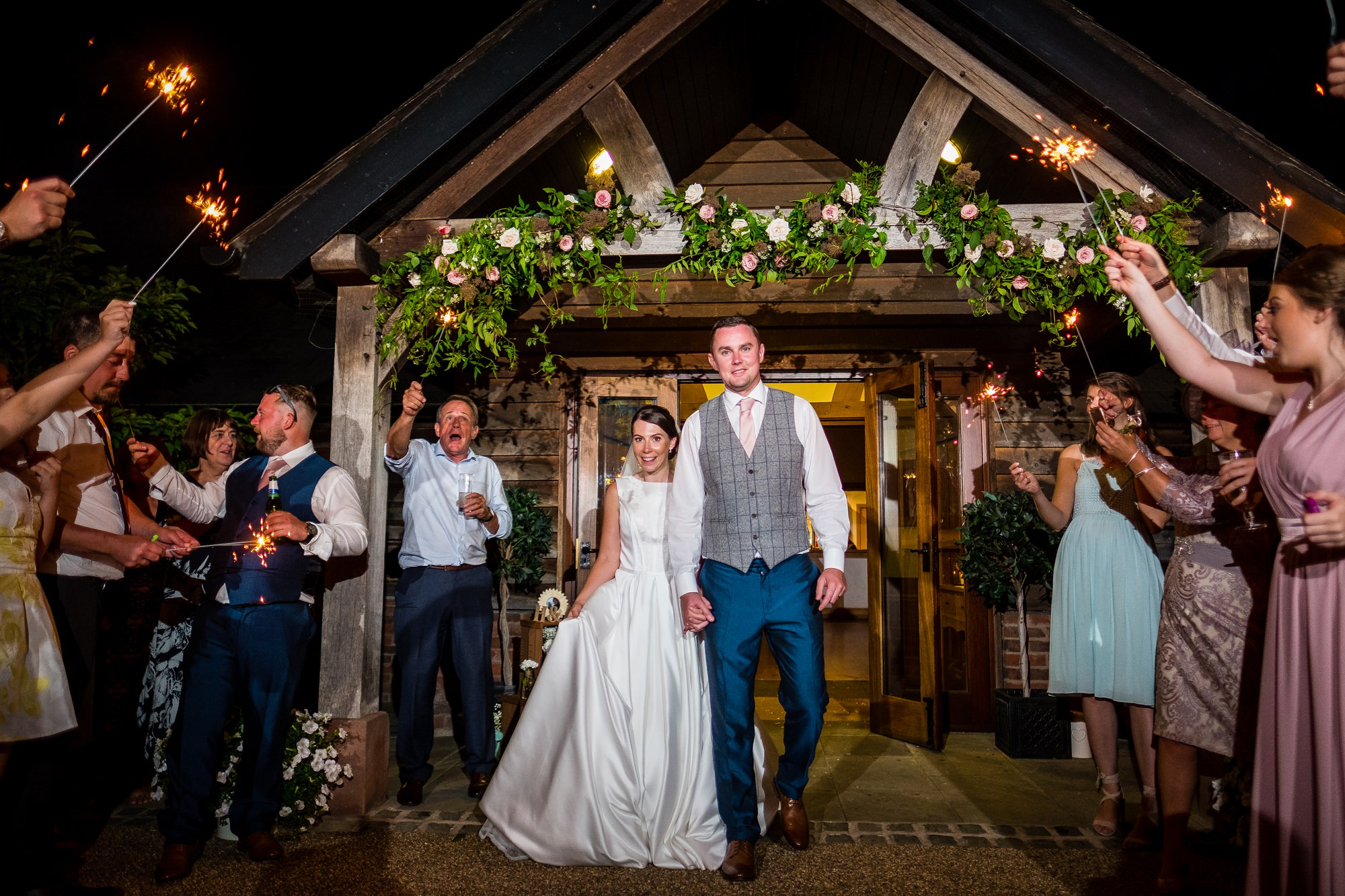 bride and groom walking through sparklers