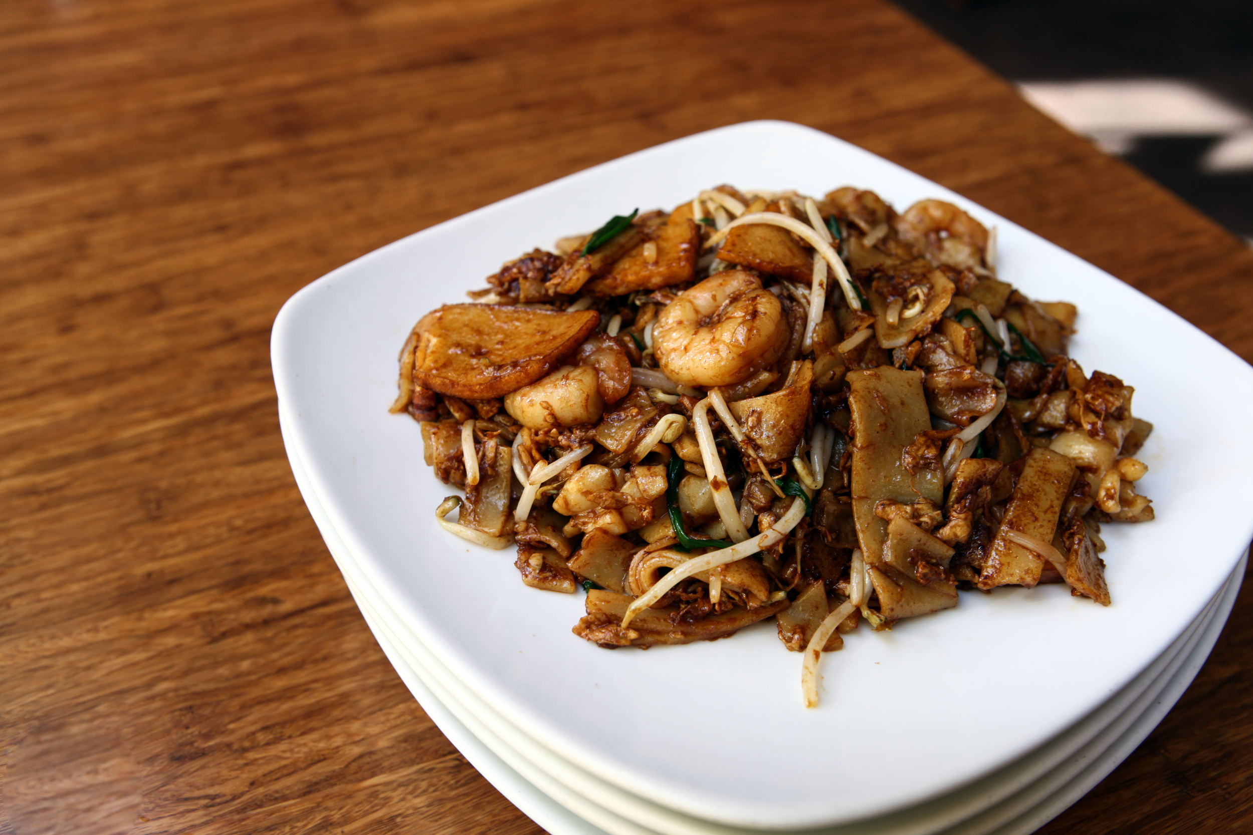 Char Kuey Teow -  Fried flat rice noodles in sweet chili and soy sauce, egg, bean sprout, shrimp, fish cake, and squid.
