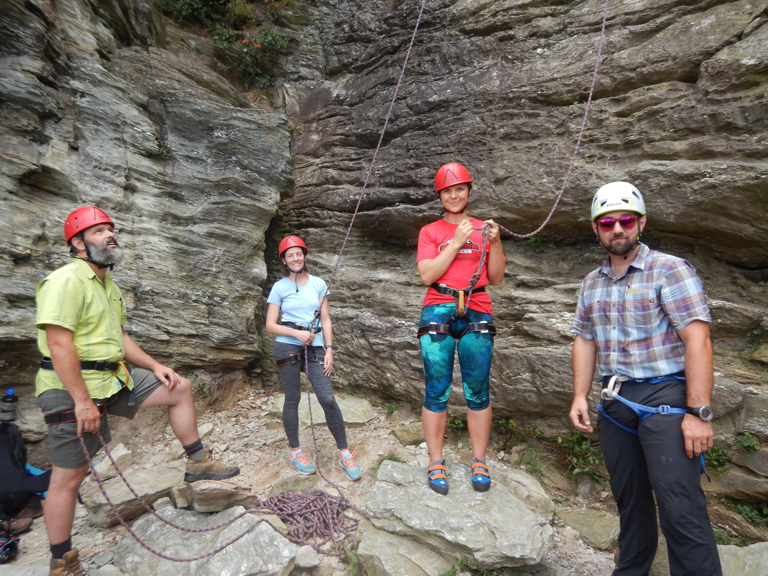 Tom instructs a rope team comprised of Molly, Stephanie, Daniel, and Lionel (not pictured here) during their day of rock climbing and rappelling.