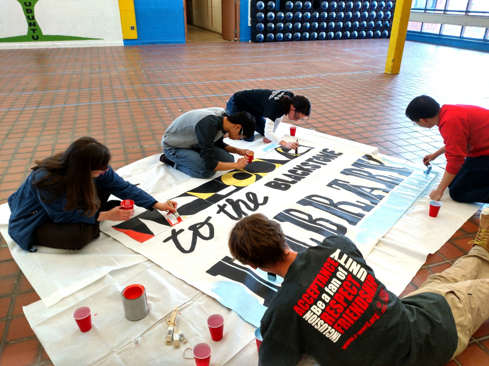 Volunteers Paint a Welcome Banner at the 6th Annual MLK Day of Action