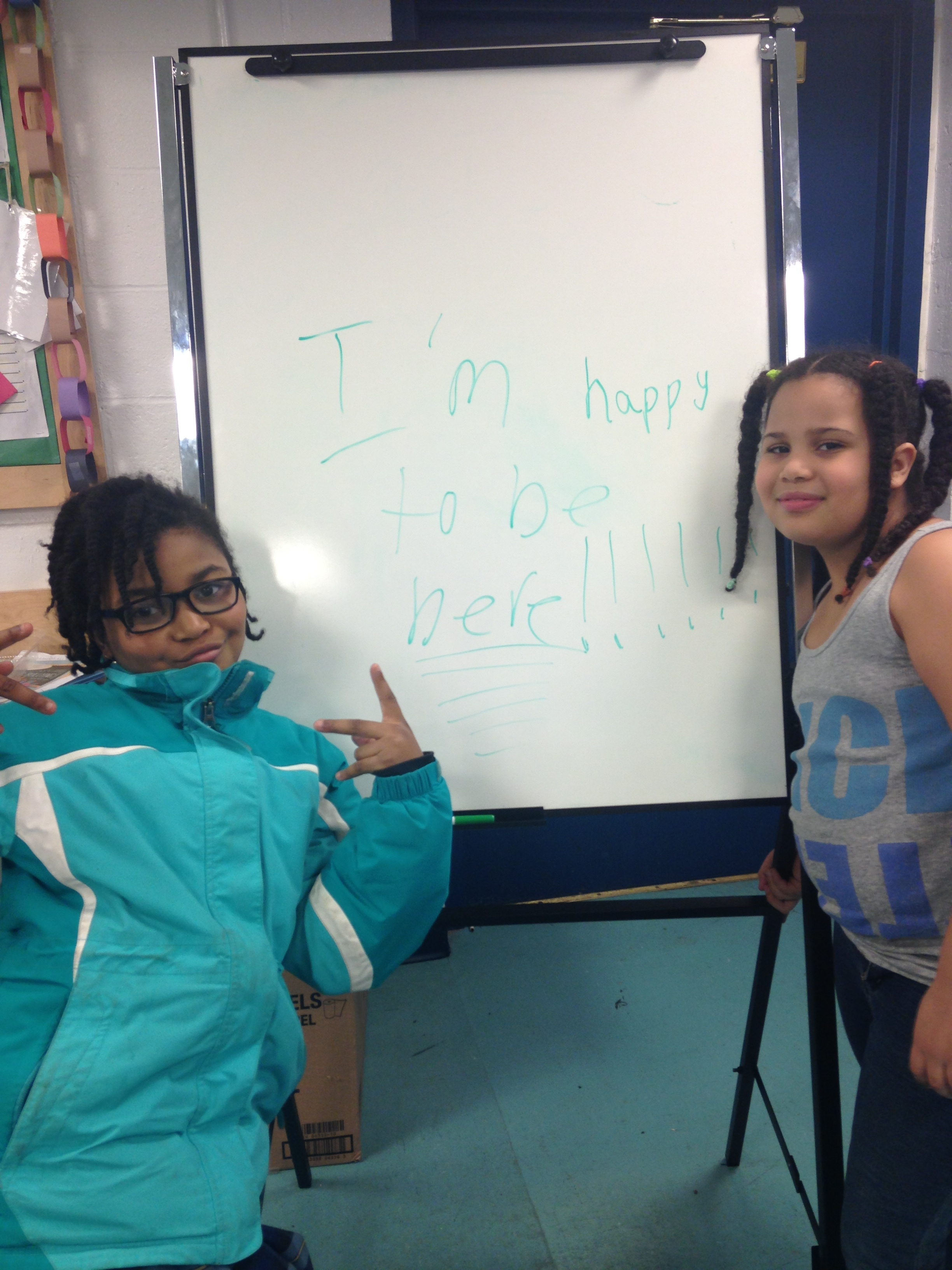 "Two students pose with their writing on a whiteboard: ""I'm happy to be here!!!!!!"""