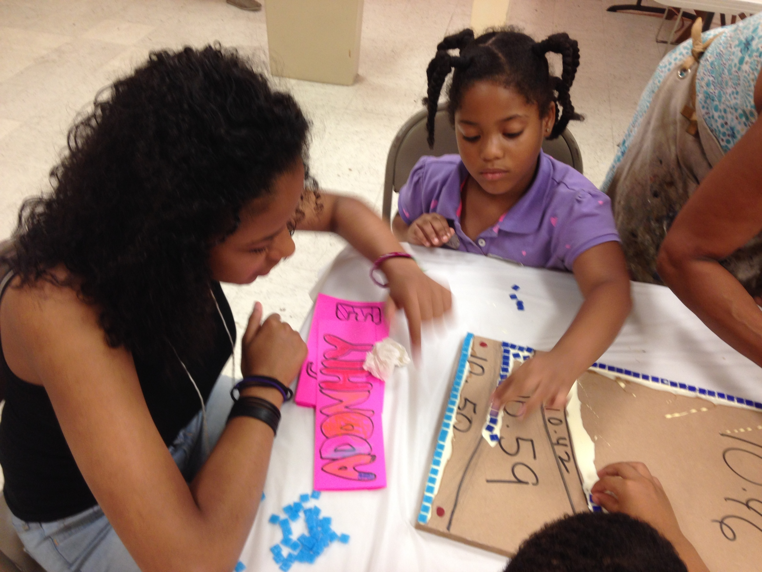 Students at St. A&M are engaged while working on a group mosaic.