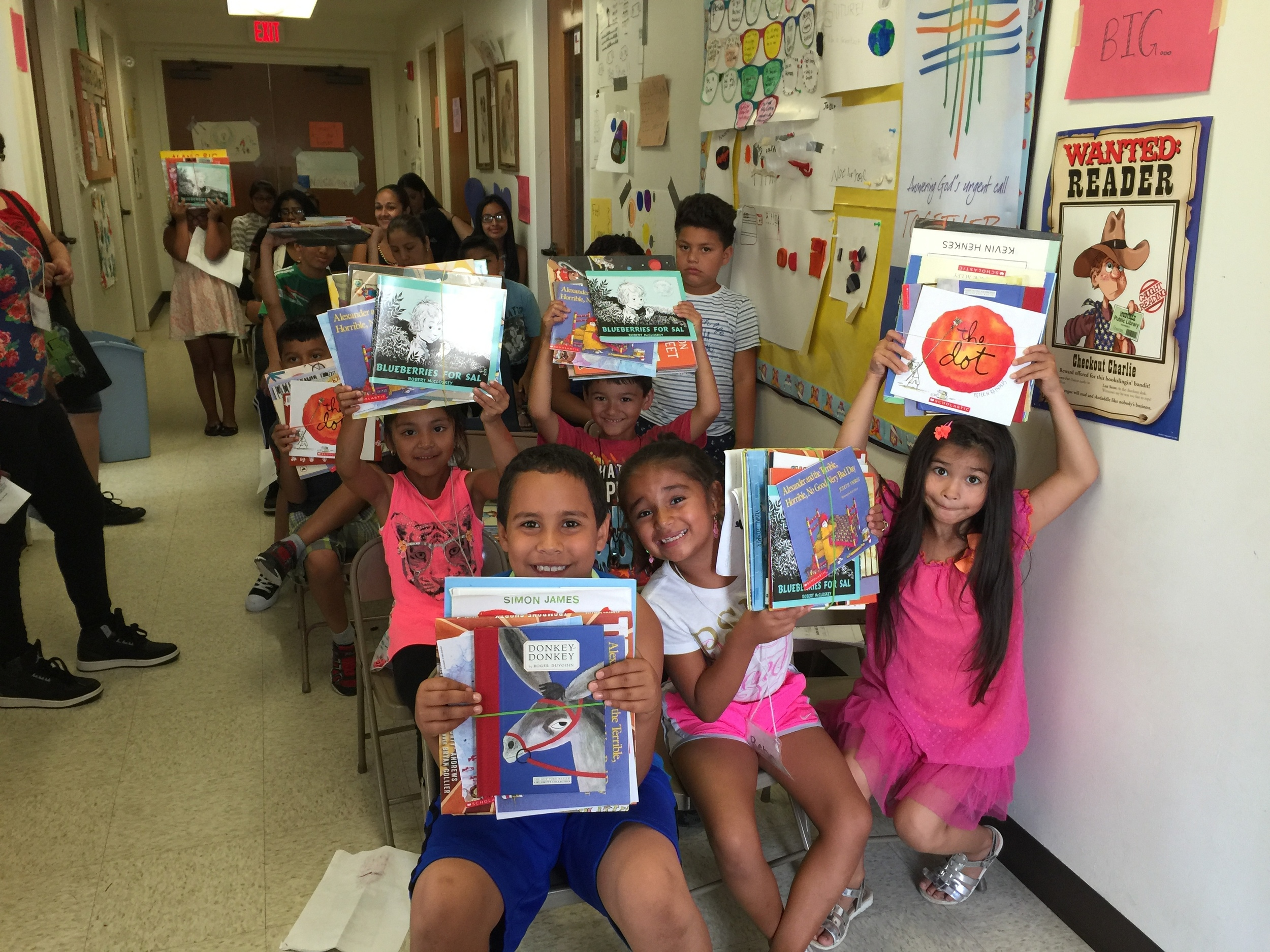 It's Christmas in July with children excited to receive books to take home and read.