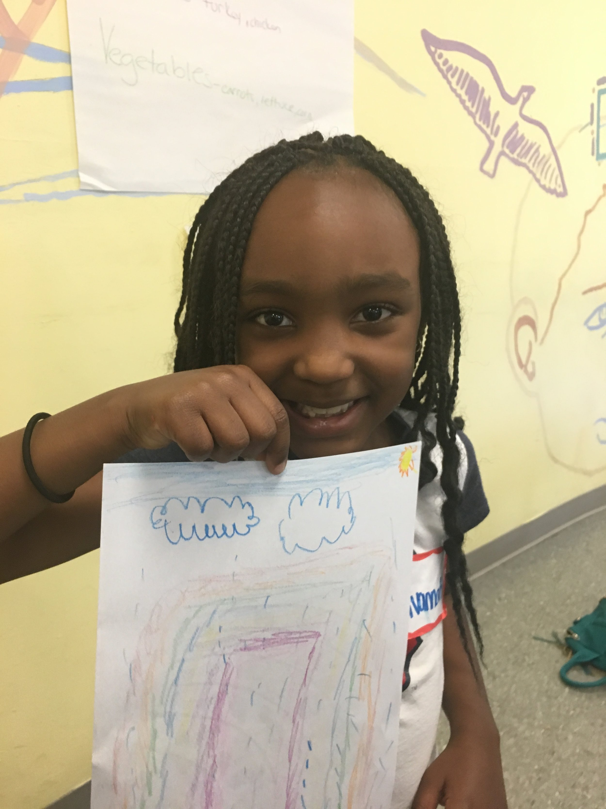 """A camper presenting her take on the rainbow after completing an activity on the foods in a """"healthy rainbow""""."""