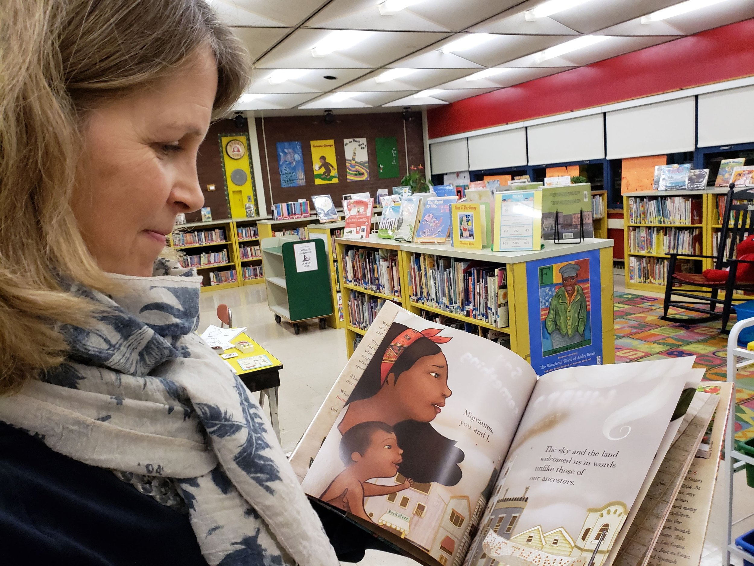 Library volunteer Jen Cusack of Needham gets ready to welcome young readers on Literacy Night