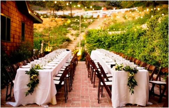 lily lodge california bay leaf garland with persimmons raspberry branches figs white table hillside outdoor wedding tamily style dining seating long table brick patio rustic.jpg