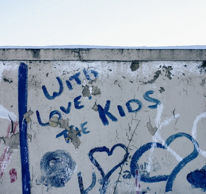 """Graffiti on wall with drawing of hearts saying """"with love the kids"""" with blue sky above"""