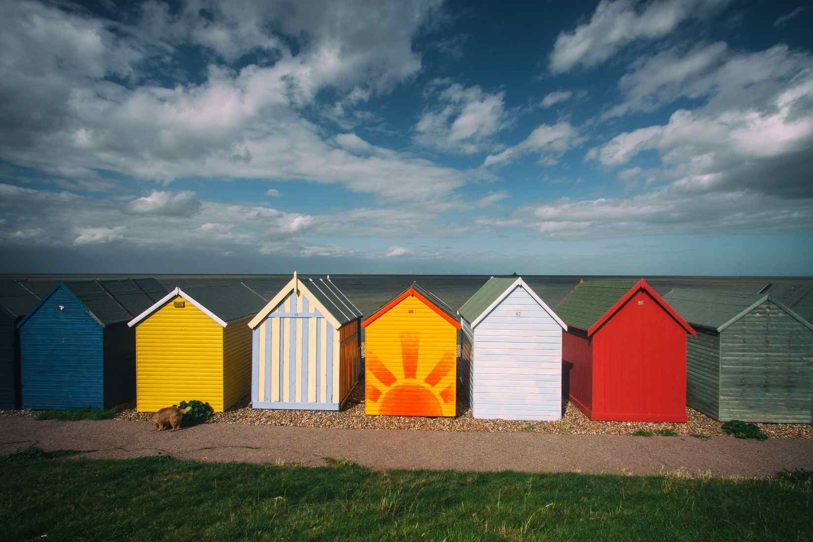 Seven small fishing huts painted in colourful ways representing different types of therapy