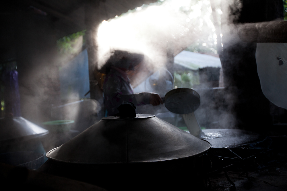 A cook shrouded in steam inside a rice noodle factory near Can Tho, April 2012.