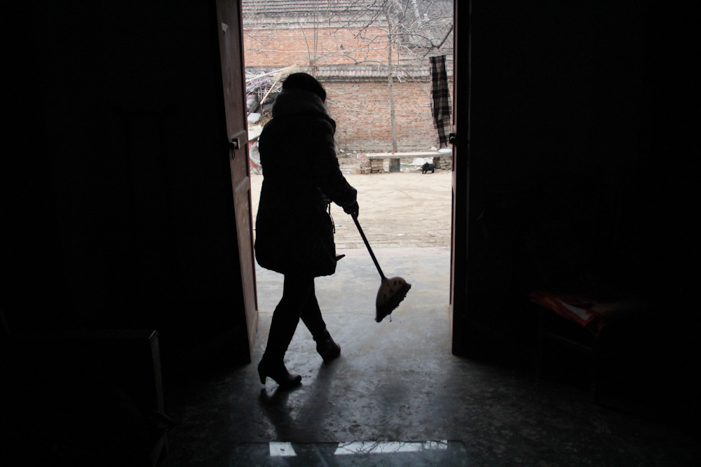 Zhang Junmei sweeping the floor and tidying up the house before the Lunar New Year celebrations, February 2013.