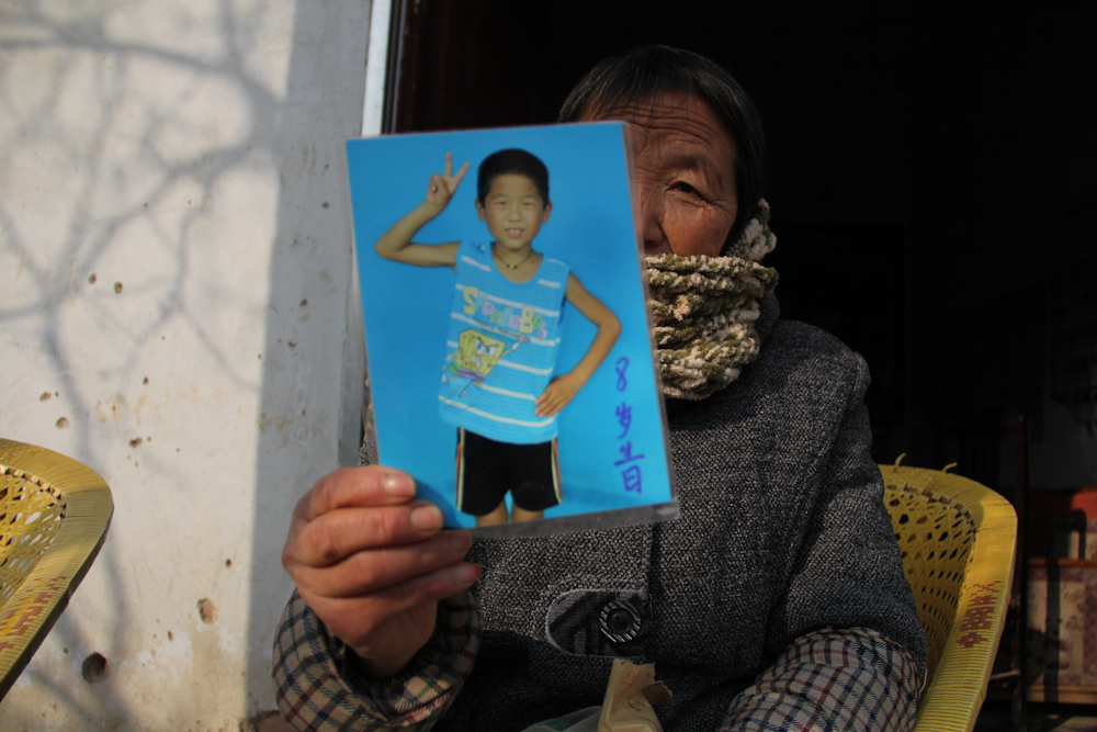 The grandmother holds a portrait of her grandson Yuan Jinkang, 10, whom she raises while her son and her daughter-in-law work as migrant workers in a factory in the southern city of Shenzhen, February 2013.
