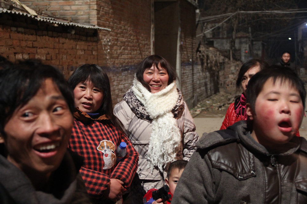 Zhang Junmei (centre) watches as her neighbours gathered outside for the traditional lunar new year fireworks, February 2013.