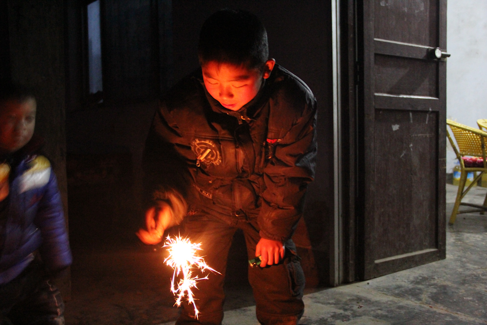 Yuan Jinkang, 10, lights up fireworks with his friends for the lunar new year, February 2013.