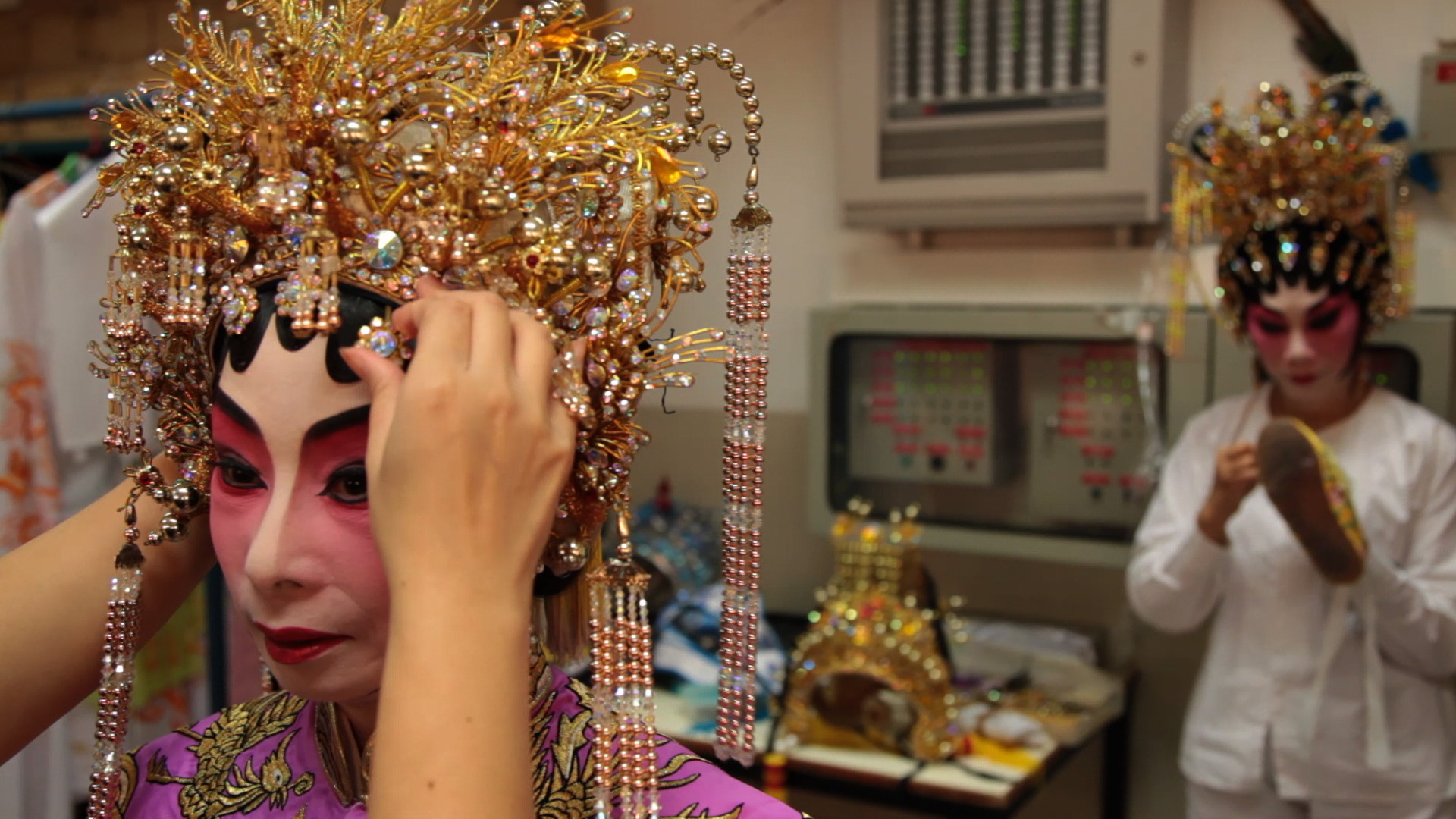 Teresa Lai Shuk-Yee, a Cantonese Opera performer, waits as a fellow artist puts the finishing touches to her hairdo before a show in September 2012 at the Koshan theatre in Hong Kong.
