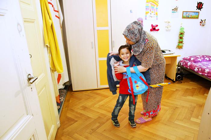 Ali se prépare pour l'école, aidé de sa maman.