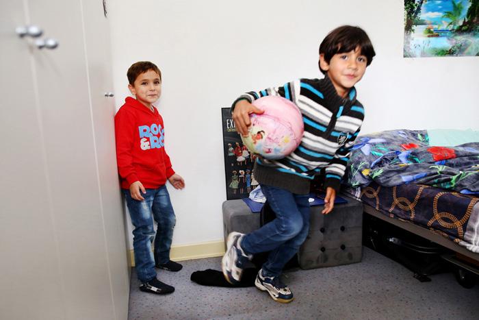 Ali joue au retour de l'école avec un des fils de la famille voisine occupant un appartement au dessus.