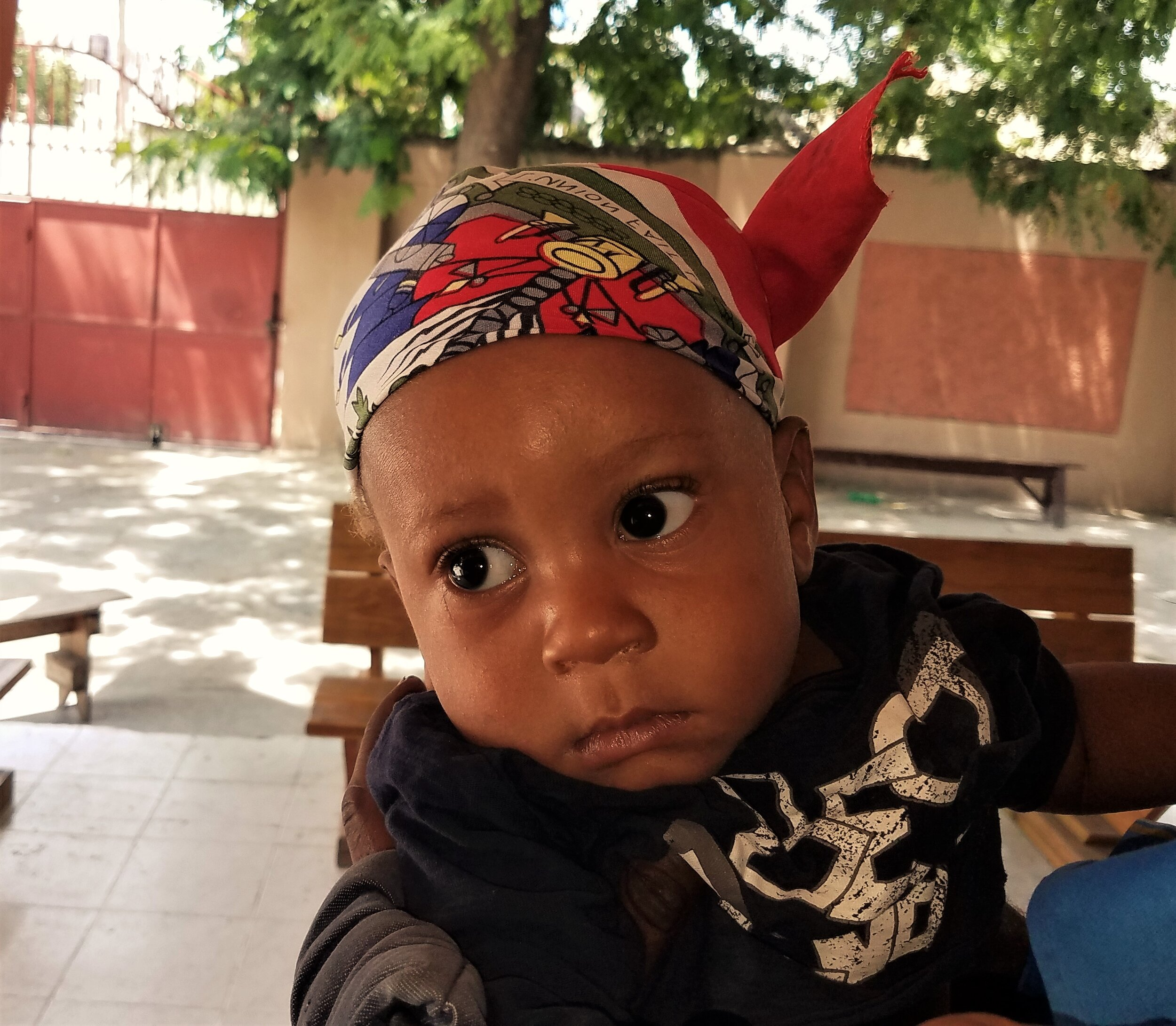 This little man is still showing his Haiti pride with his Haiti flag doo rag as he is leaving malnutrition clinic.