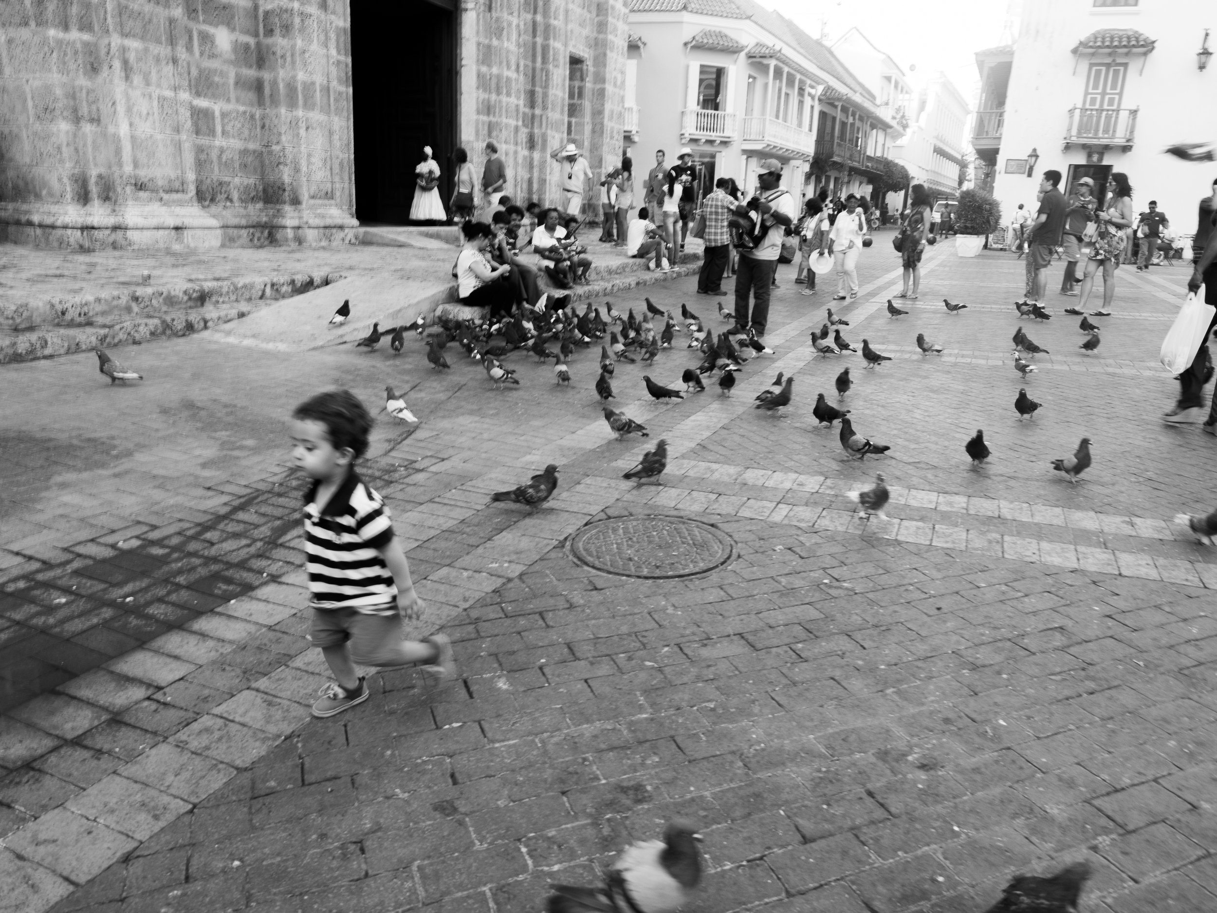 Kid playing with pigeons outside San Pedro