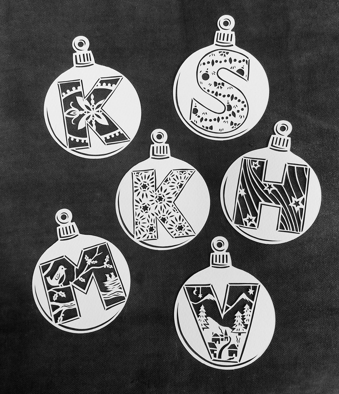 papercut illustration of holiday baubles with letters