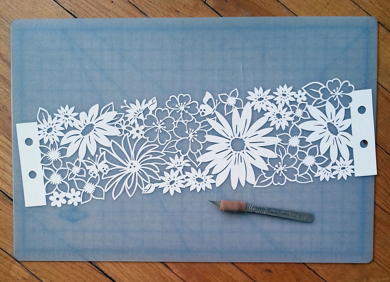 papercut illustration of floral crown on cutting mat