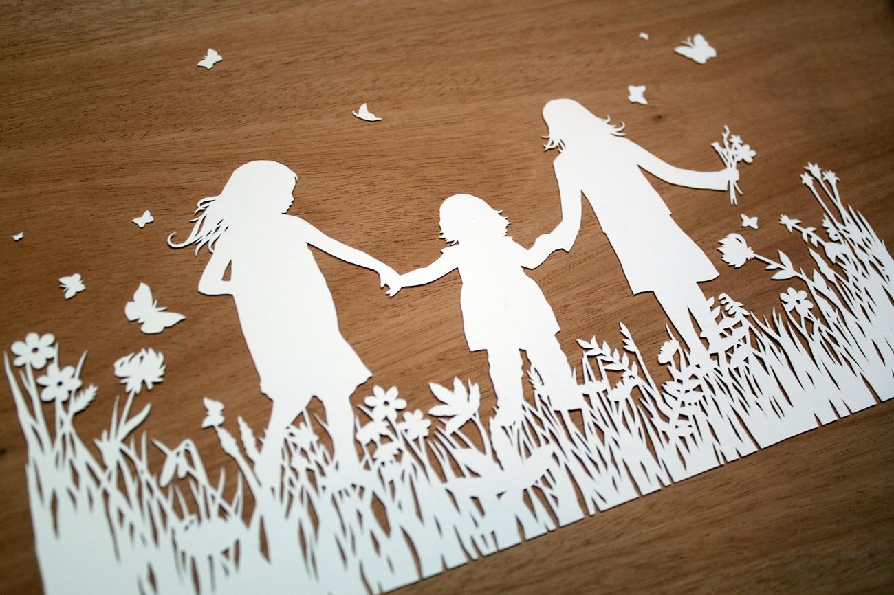 papercut illustration of three girls dancing in wild flowers
