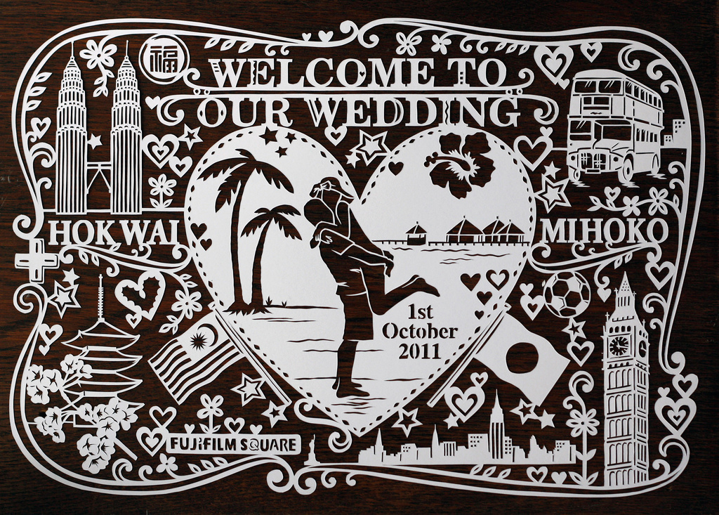 intricate papercut illustration for wedding with couple on beach