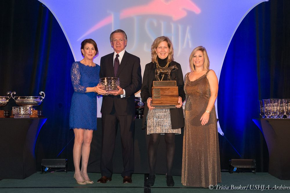 EMO's Martha Hall, left, and E. Sue Bopp, holding bronze trophy, present the USHJA Owner's Legacy Award annually at the USHJA Annual Meeting.