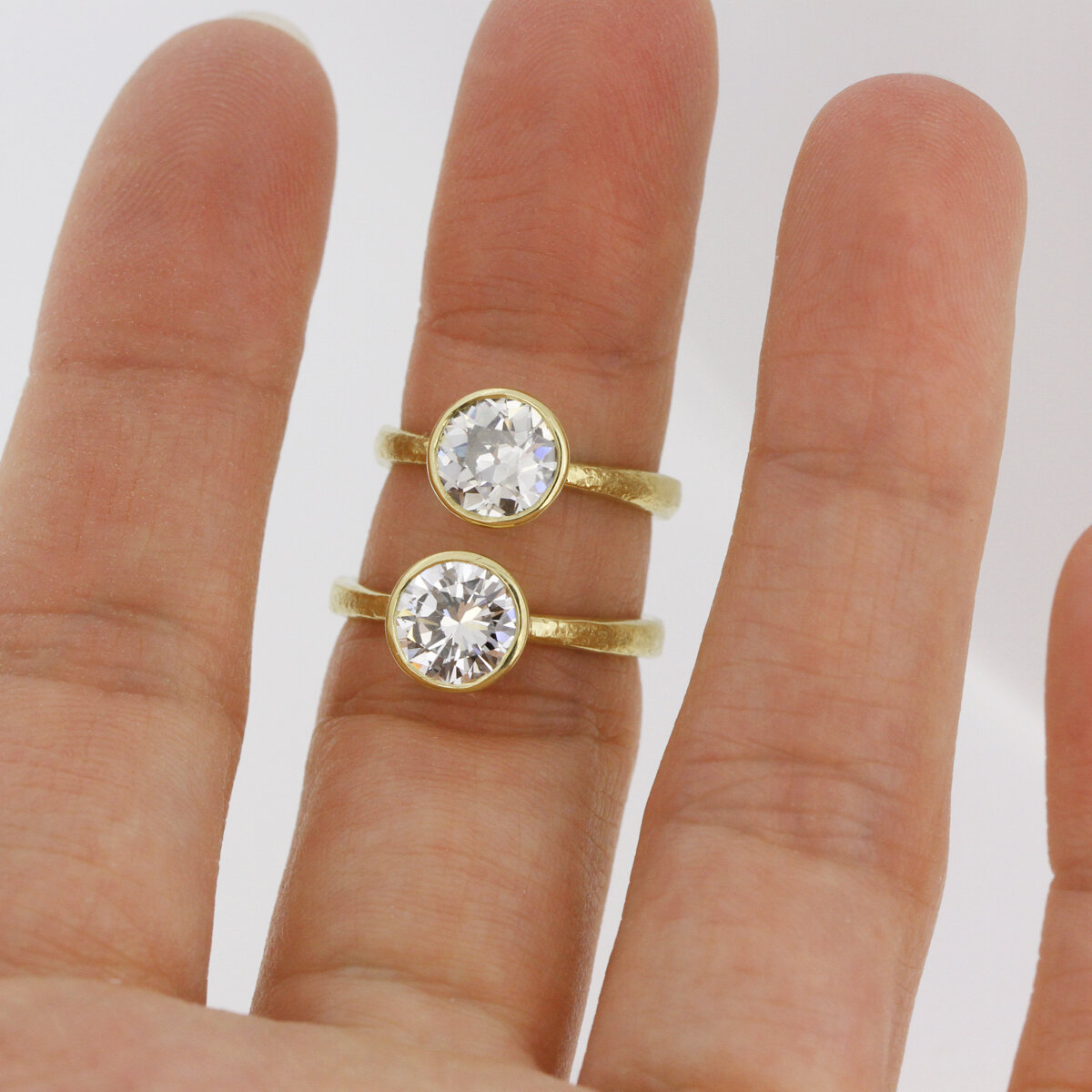Old European on top, Round Brilliant on bottom. Notice the different facet structure. The top stone has chunkier facets and you can see the culet right at the center, while the bottom stone has slimmer facets. Both 18k Custom Rings by Sophie Hughes.