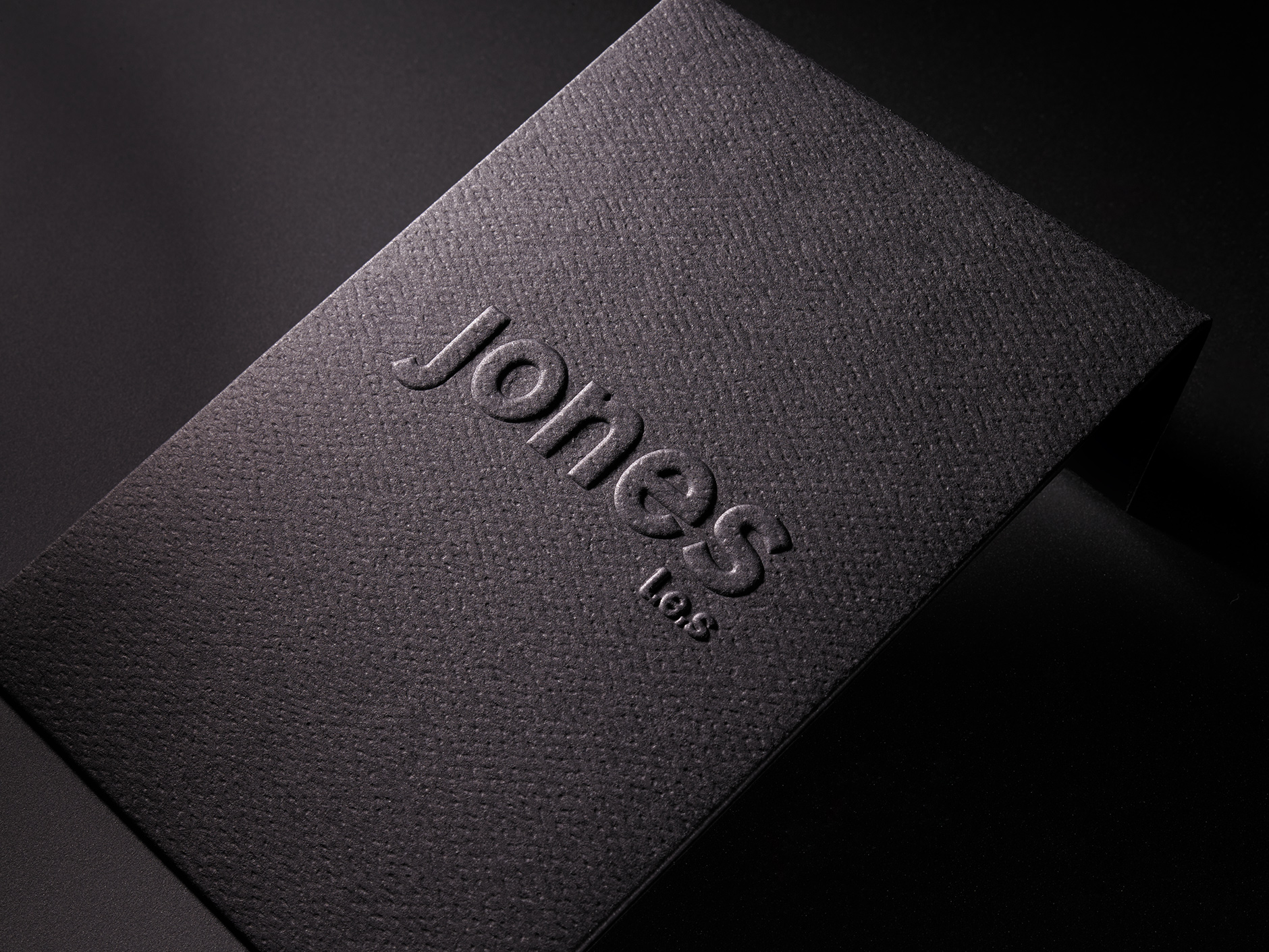 Jones L.E.S. Blind-embossed Envelope   A luxury residence on the lower eastside of Manhattan, Jones L.E.S. needed an envelope to help express their brand. The solid black textured envelope was blind-embossed with a peel and seal strip on the inside of the flap. It was custom diecut to house a mounted promotional notecard with a color image of a peacock & model on the backside of the card.
