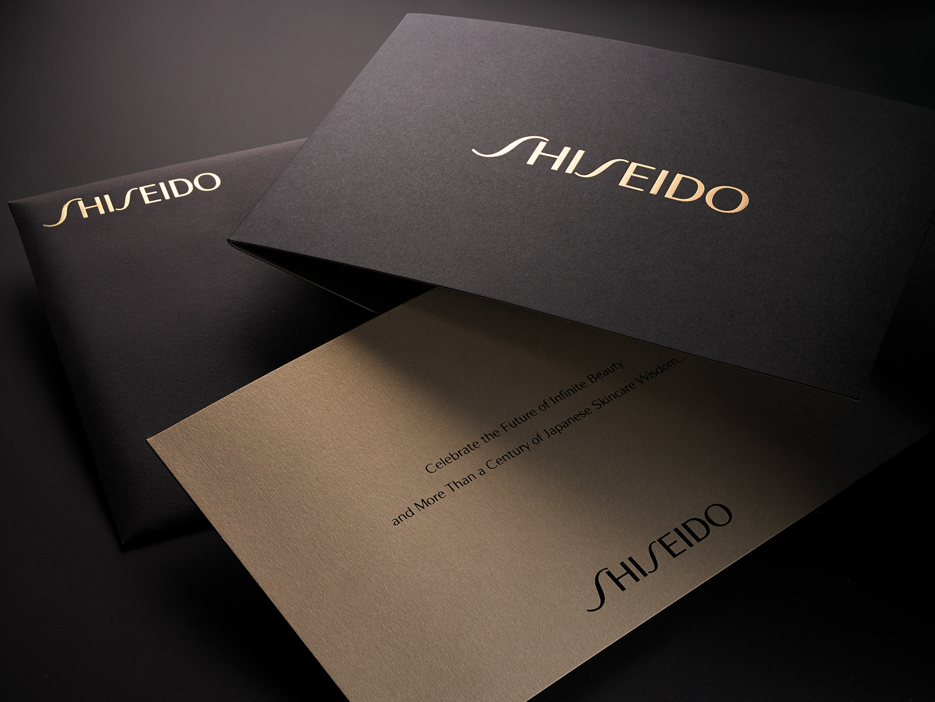 Shiseido Invite/Envelope Mailer   For this beautiful mailer we gold foil-stamped a solid black uncoated envelope with the Shiseido logotype. The invite text was also black and gold foil-stamped and mounted with a solid black and pearlized bronze cover stock. Their clients loved the substantial and luxurious feel!