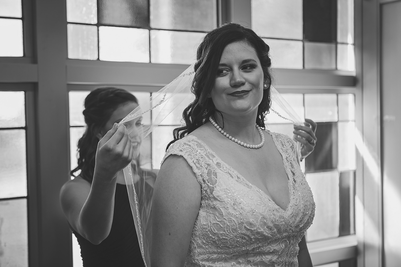 Bridesmaid helps bride with veil during wedding prep, Lake of the Ozarks, MO
