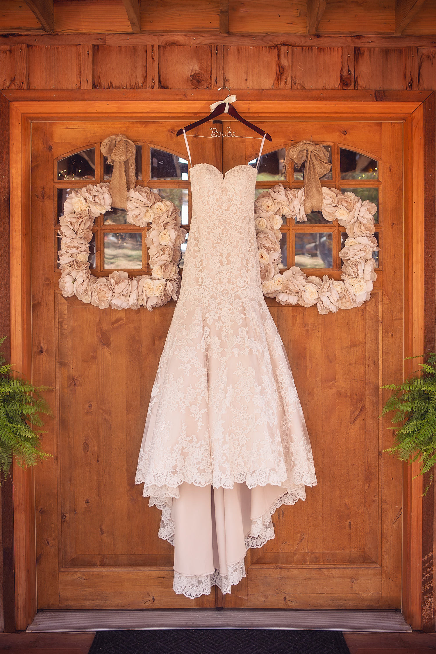 Bride's dress hangs in the doorway of the Weathered Wisdom Barn wedding venue in Buffalo, Missouri