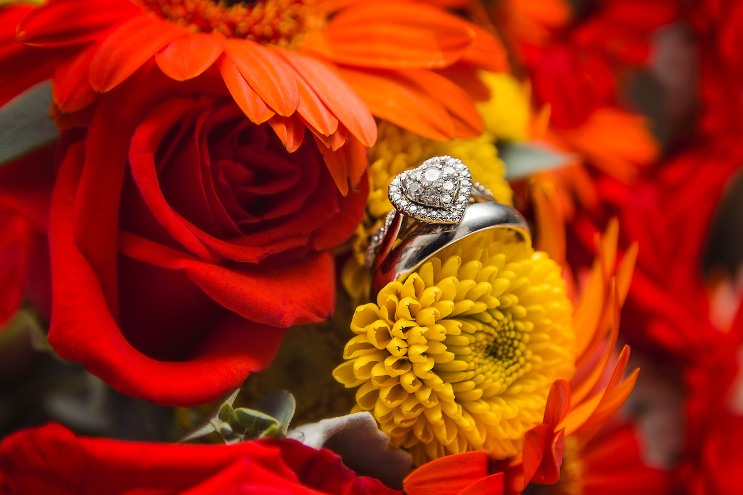 Red and orange bridal bouquet with silver heart-shaped wedding ring and wedding band