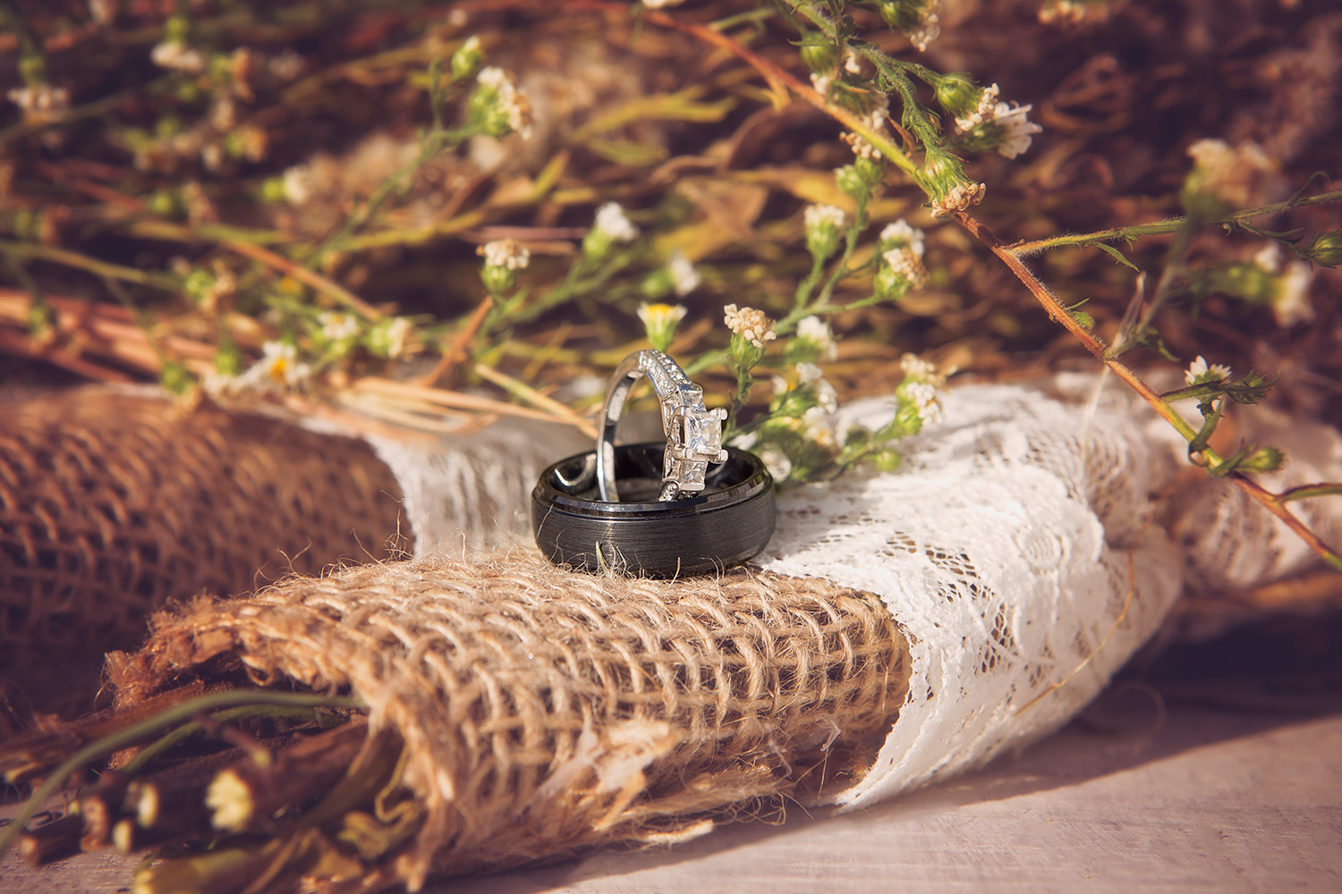 Bride and groom's rings rest on bouquets of baby's breath - Wedding Photography, Springfield, Missouri