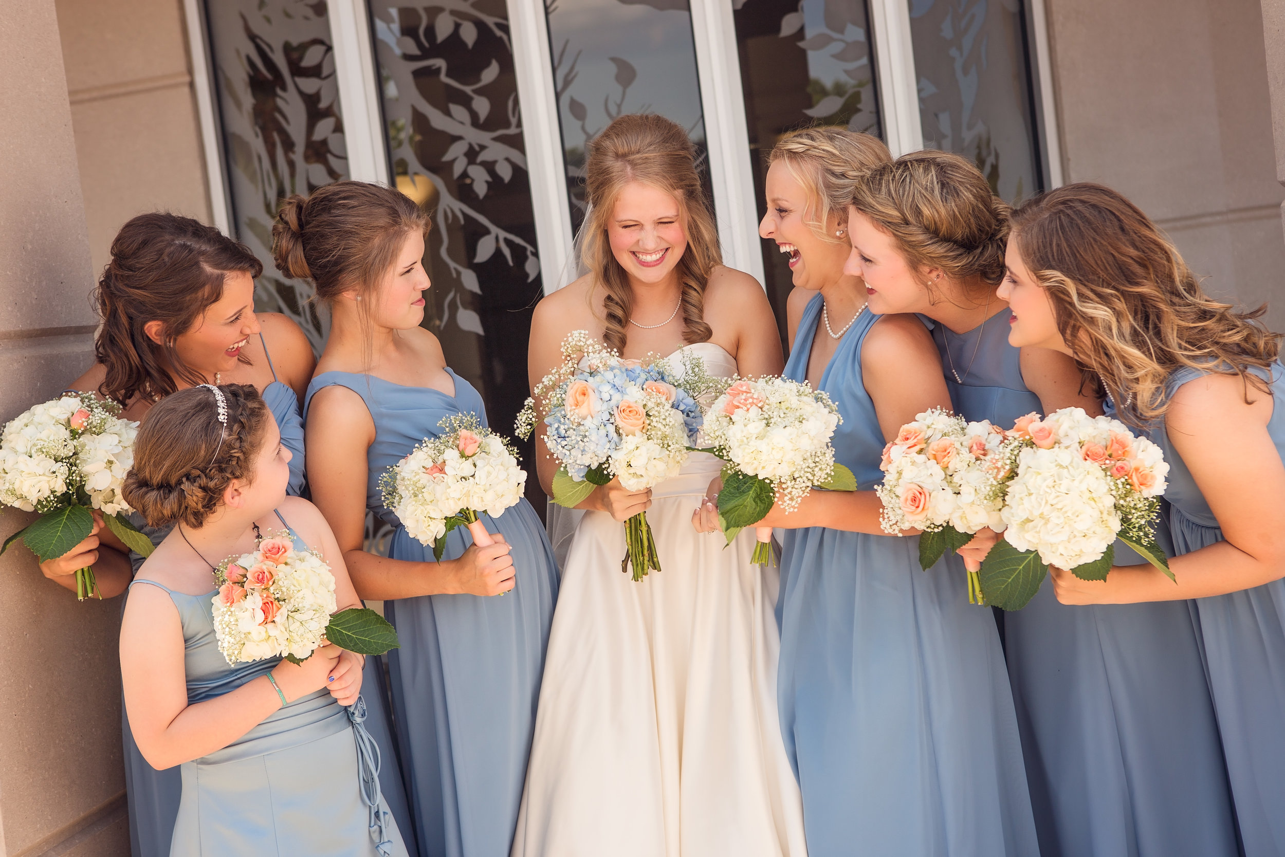 An Arkansas bride laughs with her bridesmaids during her wedding photography.