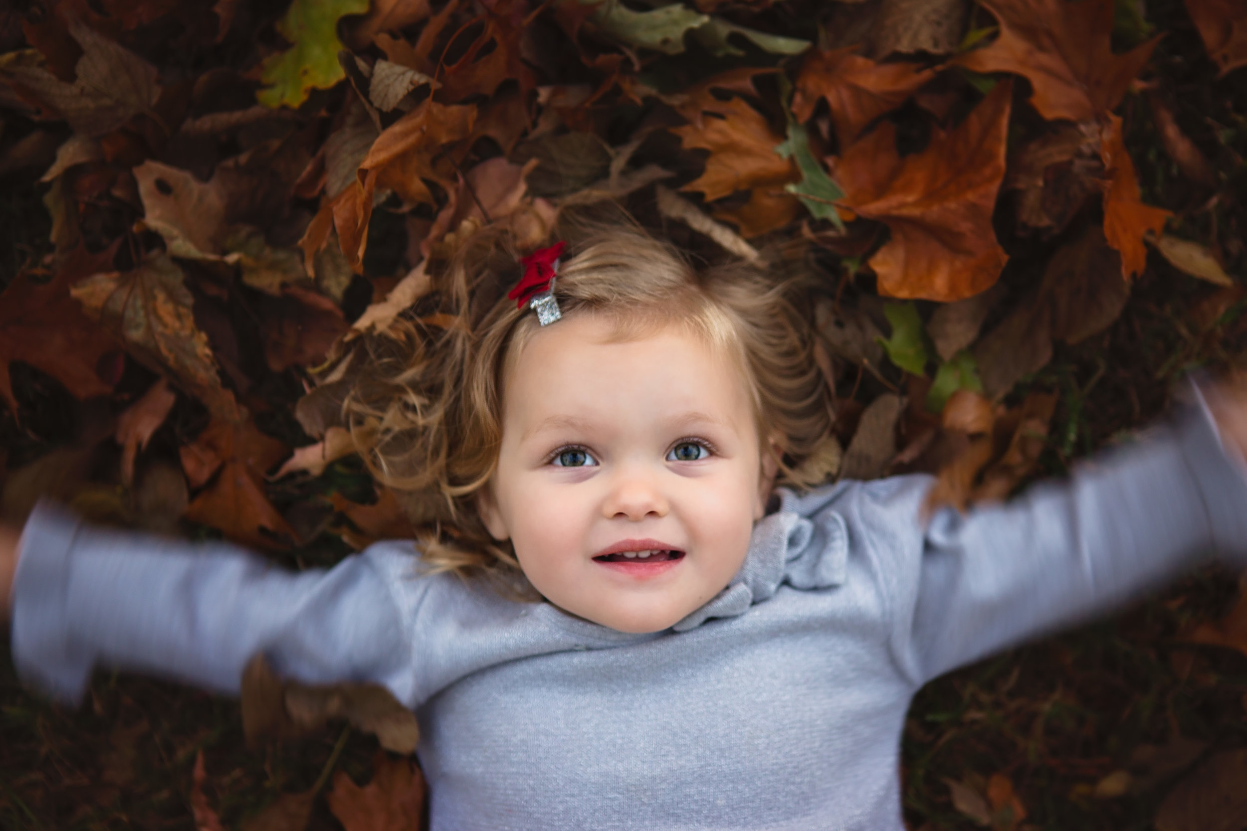 Young girl lies on her back looking up while she moves about in a pile of fall colored leaves