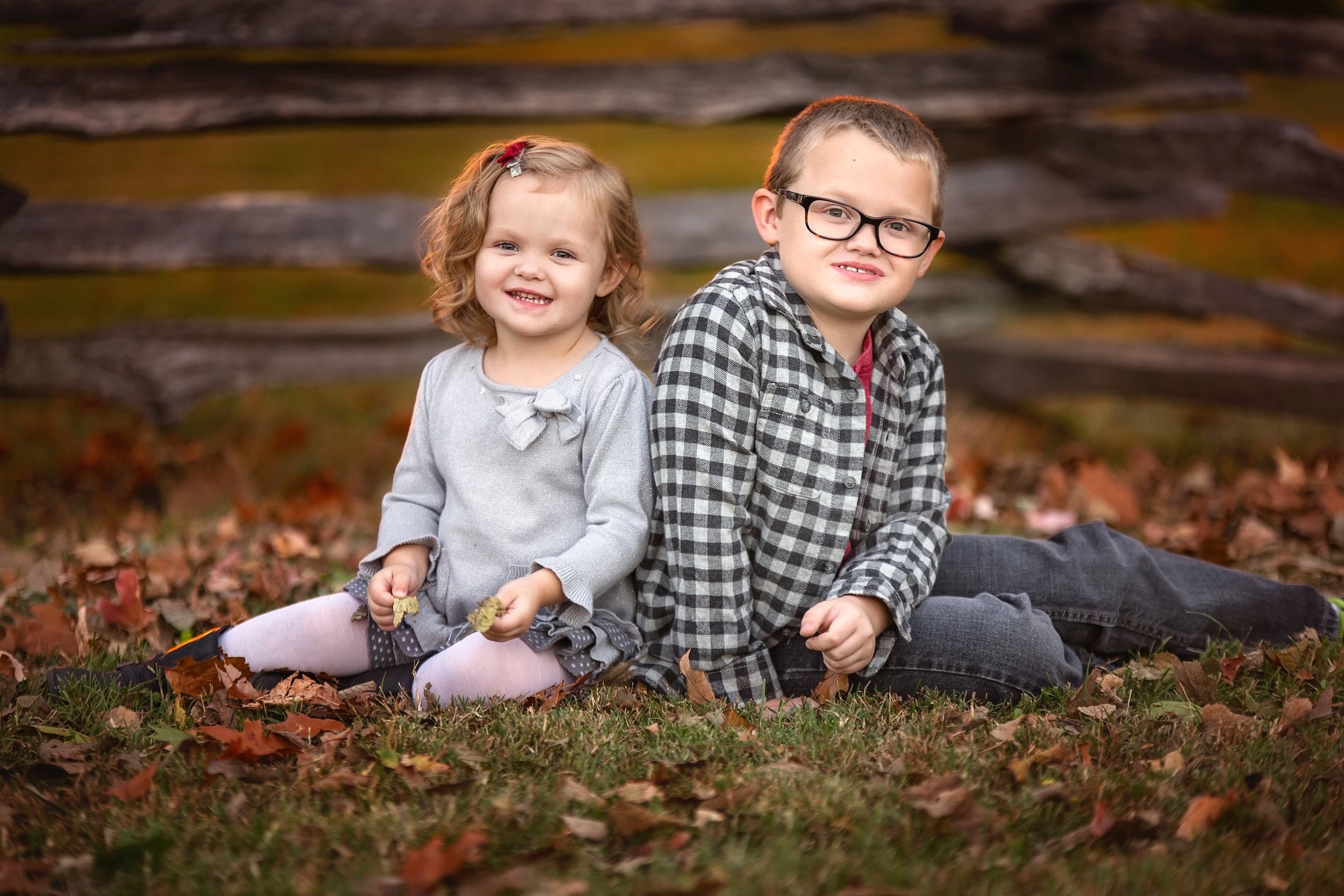 Brother and sister pose back to back in fall colored leaves in front of a wooden fence during their fall family session in Springfield, MO