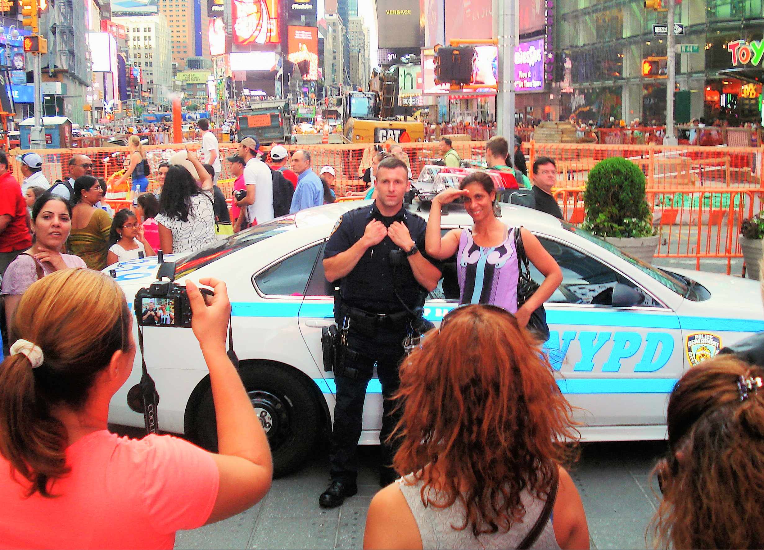 Tourists love to taking pictures with NYPD officers. Guess they love it, too